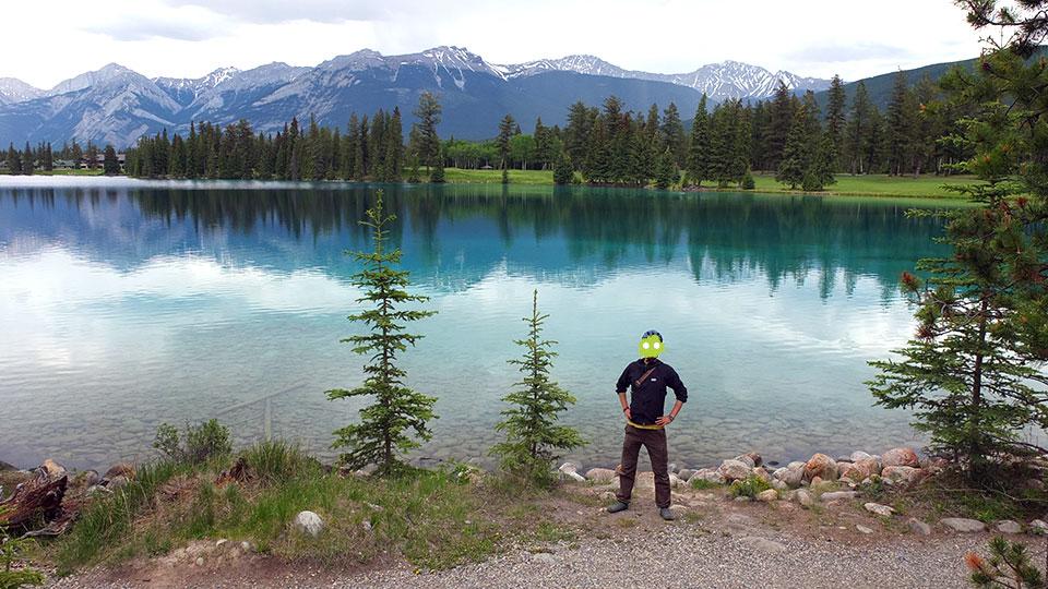 グリーンの湖と芝生、山頂に雪が残る山々。
