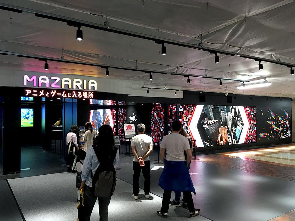 3Fエスカレーターを上がると目の前に大型スクリーンでレトロでクラシカルなドット絵たちが動き回る「MAZARIA(マザリア)」入り口が!