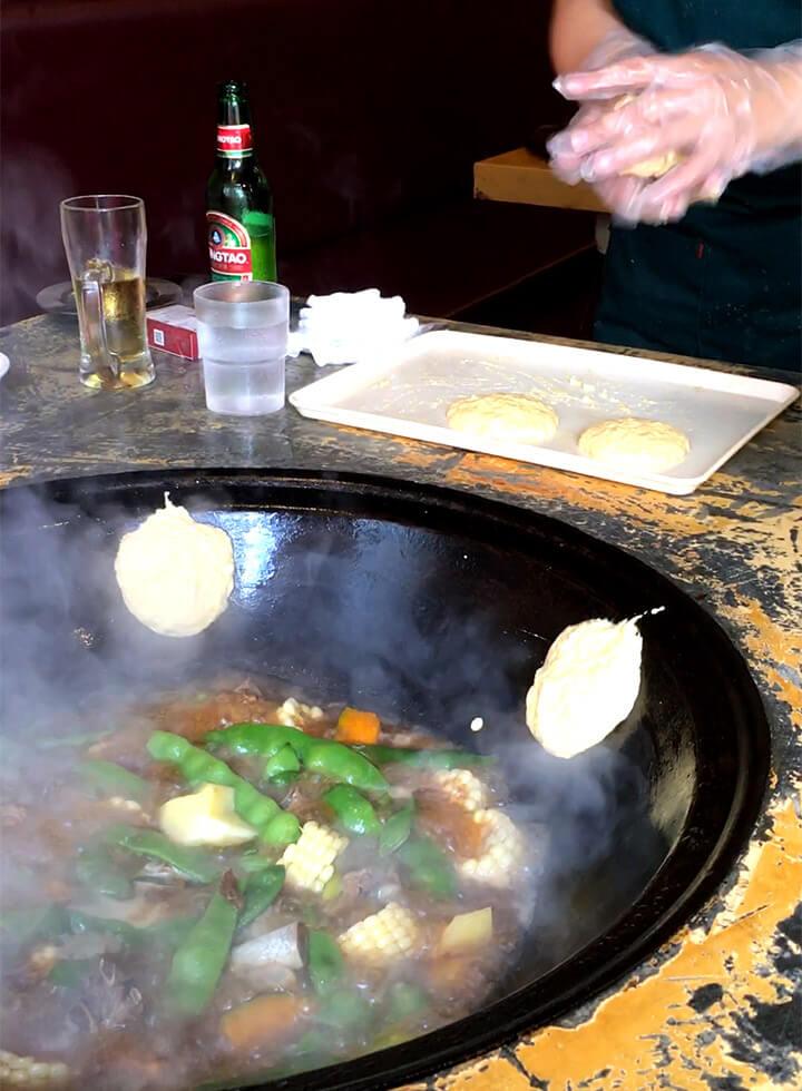 更に数十分後に店員さんが鍋の蓋を開けて、こねたトウモコロシベースのタネを「ぺちん!」と鍋側面に張り付けていきます。